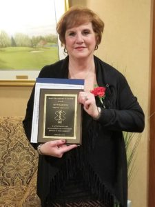 Community Outreach Coordinator Beth Sardone holding her award from the Webster-Fairport B.P.O. Elks